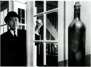 Рене Магритт, держащий яблоко за стеклянной дверыо своего брюссельского дома. Апрель, 1967